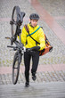 Male Cyclist With Bicycle And Courier Bag Walking Up Steps