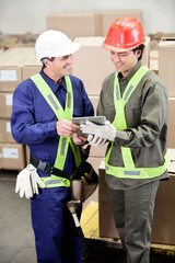 Foremen Using Digital Tablet in Warehouse