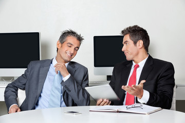 Businessman Holding Digital Tablet Sitting With Colleague At Des