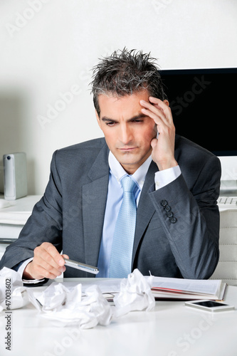 Tensed Businessman Sitting At Desk