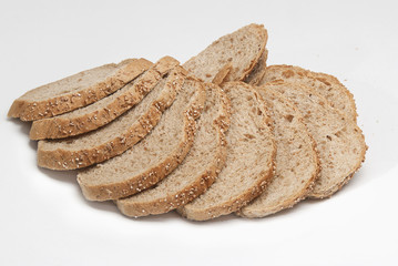 loaf of rye bread cut on pieces on a white background