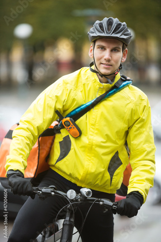 Young Male Cyclist With Courier Delivery Bag On Street