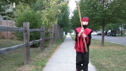 Boy in Ninja Costume Swinging Stick