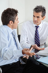 Young Businessman And Colleague Discussing Paperwork