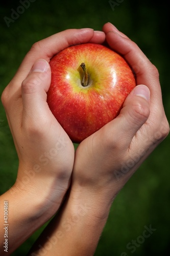 Hands of a young woman and an apple.