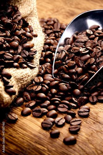 Kaffeetasse und geröstete Bohnen auf Holztisch - Kaffeegenuss