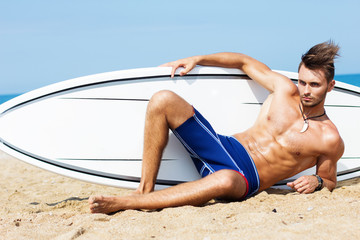 Strong young surf man portrait at the beach with a surfboard