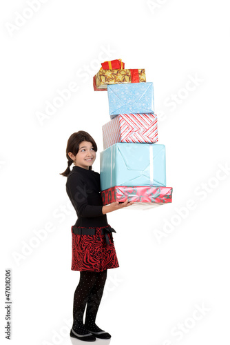 Little girl carrying huge pile of christmas presents