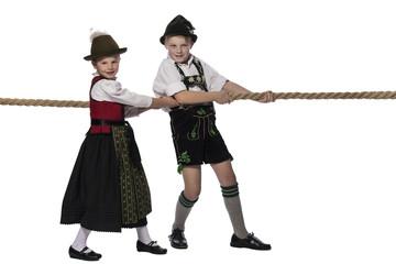 Mädchen und Junge in Allgäuer Tracht beim Seilziehen