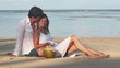 Attractive couple with coconuts sitting on beach