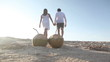 Two coconuts placed on sand and couple walking