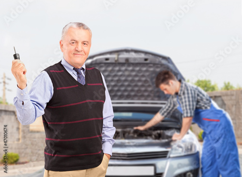 Mature gentleman holding a key while in the background mechanic