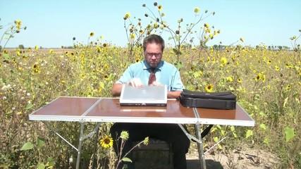 Businessman in Office Outside in Sunflower Field