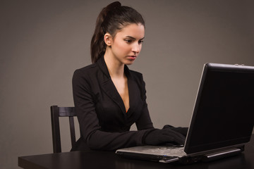 Spy girl in a black with laptop