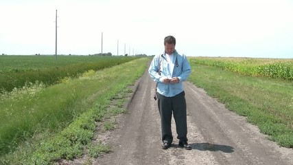 Businessman Dressing on Dirt Road at Field