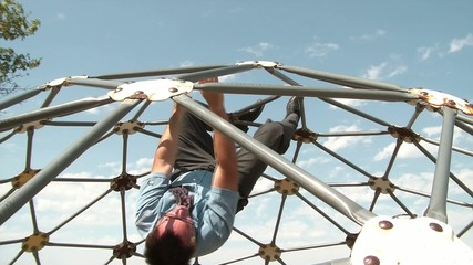 Businessman Hanging Upside Down at Playground