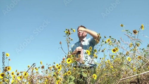 Businessman Looking Through Binoculars in Sunflowers