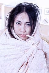 Woman with fever and thermometer wrapped in blanket
