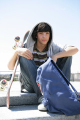 Boy sitting on a step with skateboard