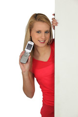 woman with an open cellphone and board for message