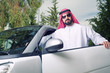 arabian guy posing against his car at home