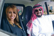 Arabian couple smiling in their car