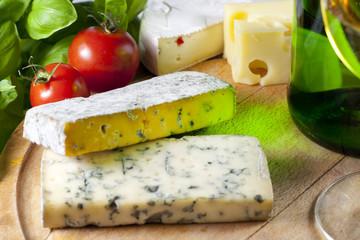 Cheese on cutting board closeup with basil an wine