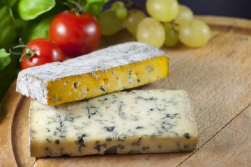 Cheese on cutting board closeup with basil