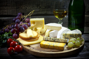 Cheese wine and grapes various assortment vintage still life