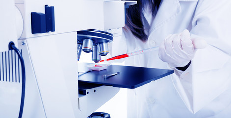 Closeup of female scientist working on a microscope  laboratory