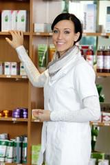 Apothekerin steht vor Regal und zeigt auf Medikament