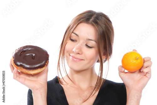 Woman comparing unhealthy donut and orange fruit