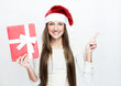 young smiling woman in santa hat , holds christmas gift