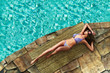 Beautiful woman sunbathing by a tropical swimming pool.