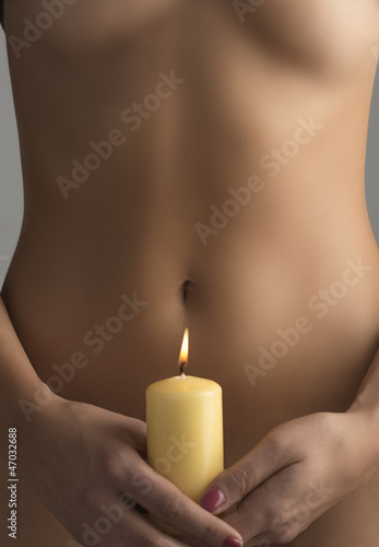 girl with candel near belly, taked with both hands