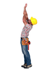Laborer trying to touch the ceiling, studio shot