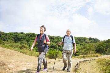 happy asian senior couple hiking