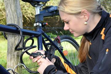 Junge Frau schließt Fahrrad ab