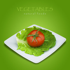 Savoy cabbage and tomato in plate on green background