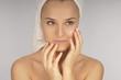 Beautiful woman in a white towel applying moisturizer cream on f
