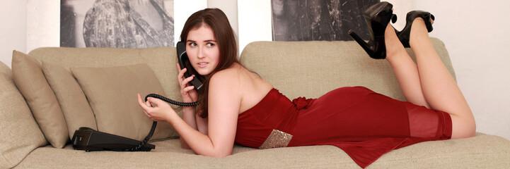Hübsche Frau im Abendkleid beim Telefonieren