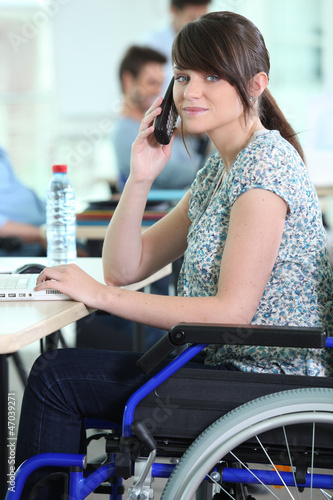 Young woman in a wheelchair at her desk