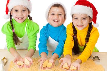 Three smiling kids showing dough