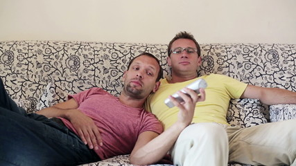 Gay couple lying on sofa and watching tv