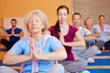 Seniorin in Yogakurs im Fitnesscenter