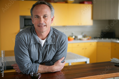 Man leaning on kitchen surface