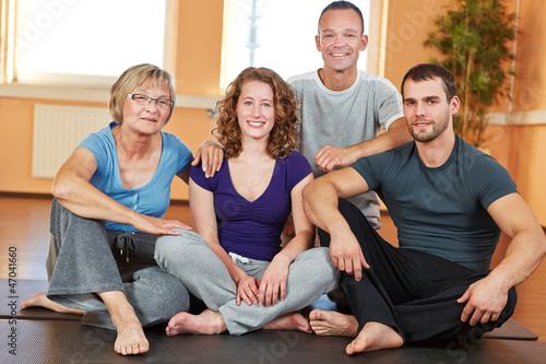 Gemischte Gruppe sitzt im Fitnesscenter