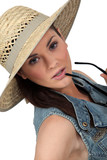 Flirtatious brunette wearing straw hat