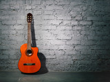 Acoustic guitar leaning on grungy wall - 47043633