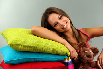 beautiful young girl and fluffy bear with pillows